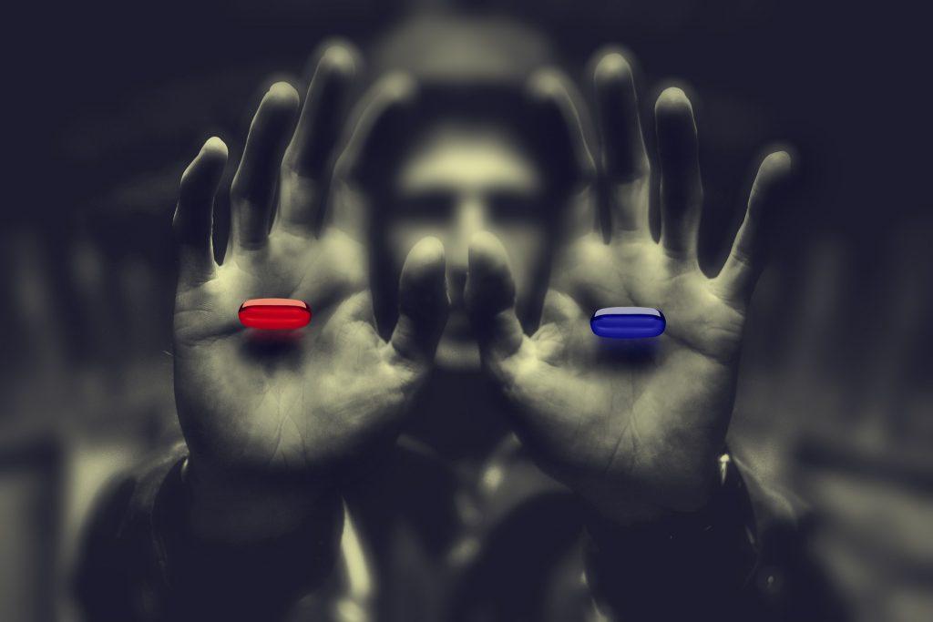 Un encapuchado te ofrece dos pastillas que flotan en las palmas de su manos, una roja y otra azul. Los colores resaltan sobre los tonos grisáceos del fondo en el que se funde el misterioso sujeto.